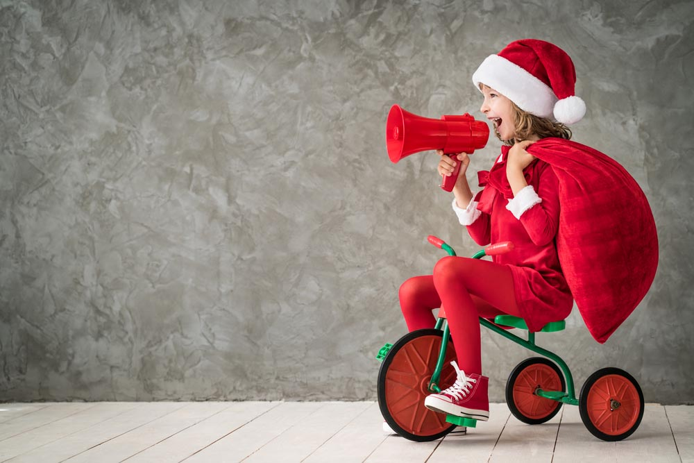 Little Girl Playing Santa on a Tricycle | The Joy of Giving supports families in need in Collier County