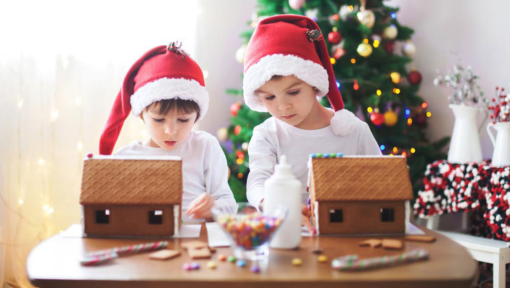 Two boys building a gingerbread house | The Joy of Giving supports families in need in Collier County