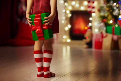A girl holding a present for Christmas | The Joy of Giving